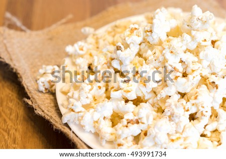 A selected focus of a popcorn on white plate and wooden table