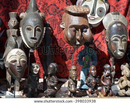 A selection of African masks and statues at a flea market on a red background - stock photo