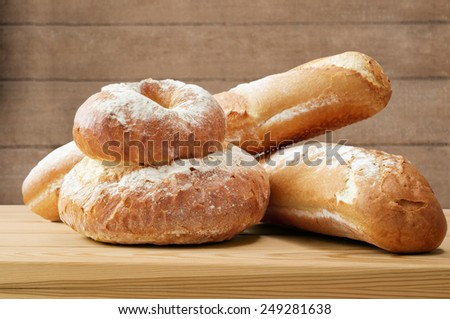 A selection of bread loaves on a wooden table in a rustic setting with wood planked wall in soft focus background. - stock photo