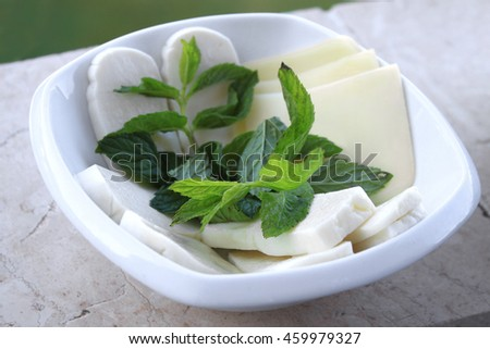 A selection of cheese with mint in a white plate.