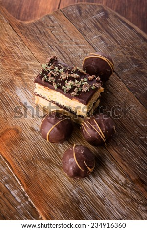 A selection of delicious chocolate truffles and cake served on a wooden board. - stock photo