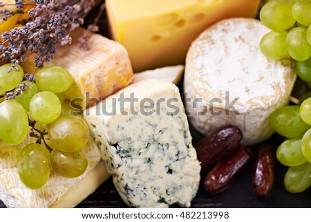 a selection of fine cheese with grapes, date fruits and lavender on a black wooden table with the wooden board. Close view