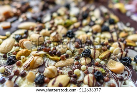 A selection of fruit and nut topping on a chocolate slab.