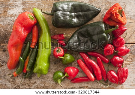 A selection of hot Chili Peppers of different varieties and colours on a wooden background