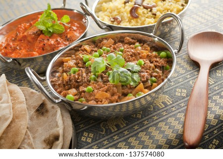 A selection of Indian curries in Balti dishes or karahi. These are keema mattar (mince with peas), chicken tikka masala and fruit and nut pilau, with chapatis. - stock photo
