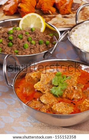 A selection of Indian foods, with lamb rogan josh, keema matar, chicken tikka, naan bread and basmati rice. Focus on lamb. - stock photo