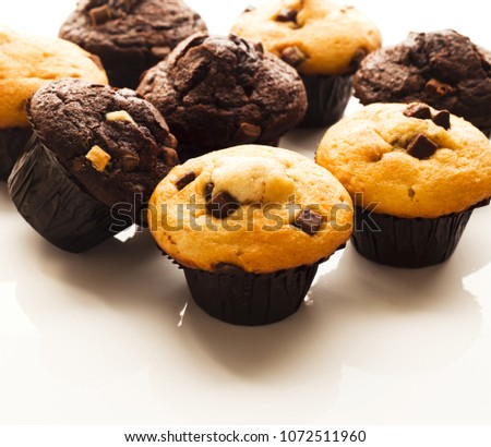 A selection of muffins on white reflective work surface, shot at angle