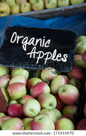 A selection of organic pink apples with a board saying organic apples - stock photo