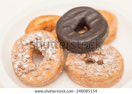 A selection of tasty, fresh donuts on a white plate - stock photo