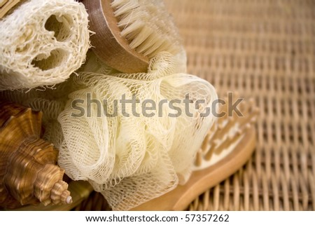 A selection of therapy products on a wicker mat with some seashells. - stock photo