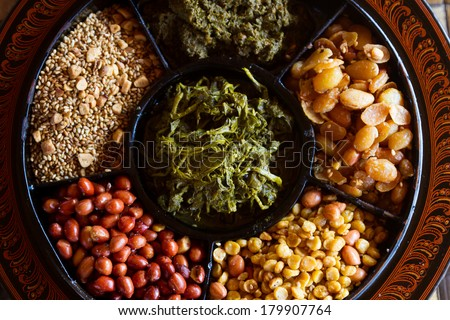 A selection of typical Myanmar snacks: tasty and spicy seeds, nuts and pickled tea leaves. - stock photo