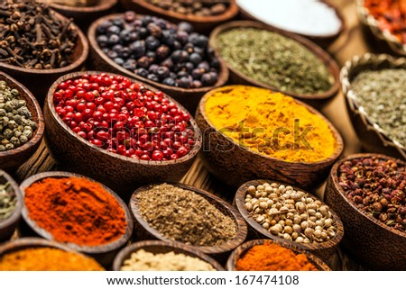 A selection of various colorful spices on a wooden table in bowls - stock photo