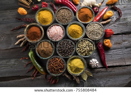 A selection of various colorful spices on a wooden table in bowls