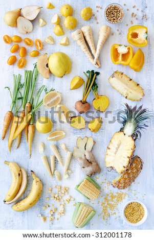 A selection of various fresh yellow raw organic produce fruits and vegetables pineapple carrot parsnip capsicum soy beans lemon tomato pear corn banana beetroot - part of a color spectrum collection