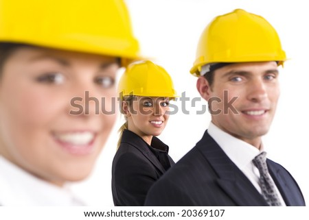 A selective focus industrial concept shot showing two women and a man dressed in hard hats. The focus is on the woman in the background