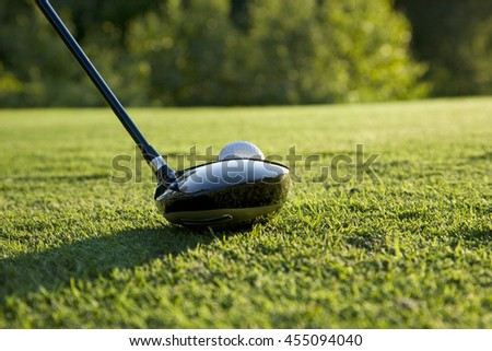 A selective focus, low angle view of a golf driver ready to hit a teed up ball