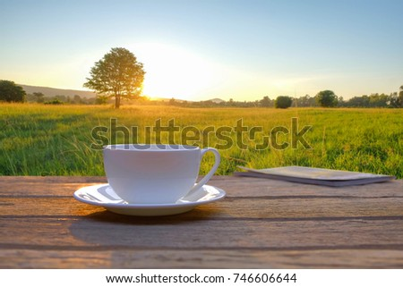 a selective focus picture of a cup of coffee on wooden table with green grass field in the morning sunrise