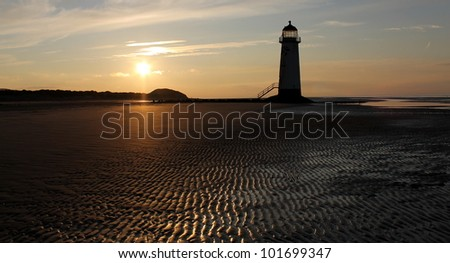 A semi silhouette beach scene at sunset with an empty lighthouse and hills in the distance.