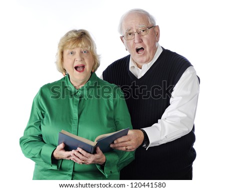 A senior adult couple singing praises together from a hymnal.  On a white background. - stock photo