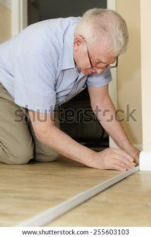 A senior adult man measuring new quarter round to replace the old on his baseboards.