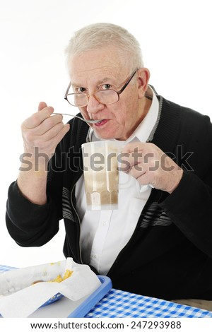 A senior adult man peering over his glasses as he eats ice cream from his root beer float.  A basket of half-eaten french fries are on the table before him.  On a white background. - stock photo
