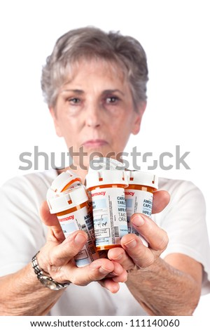 A senior adult woman shows the many medications she must take to remain healthy. - stock photo