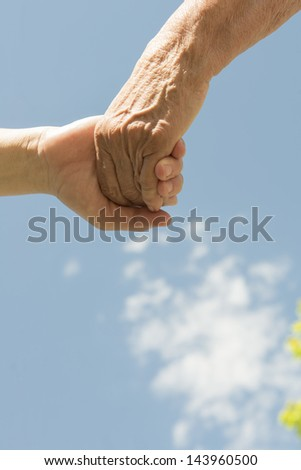 A senior and women holding hands under a blue sky with clouds. - stock photo