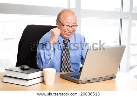 A senior asian businessman happy for success at the office - stock photo