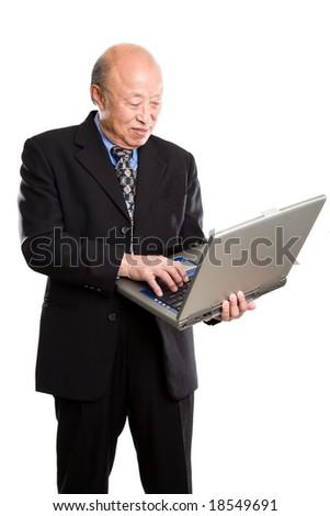 A senior asian businessman typing on a laptop - stock photo