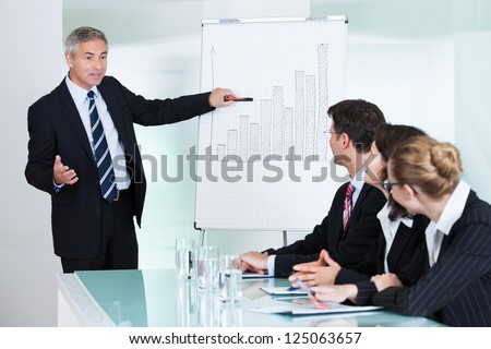 A senior business executive delivering a presentation to his colleagues during a meeting or in-house business training