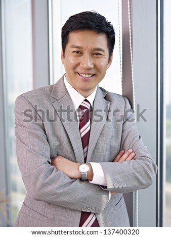 a senior business executive standing by the windows. - stock photo