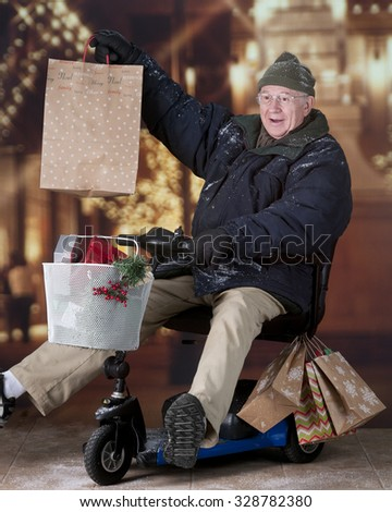 A senior Christmas shopper delighted with his purchase as he drives his scooter away from a light decorated mall.   - stock photo