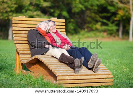 A senior couple enjoying a funny moment in a park - stock photo
