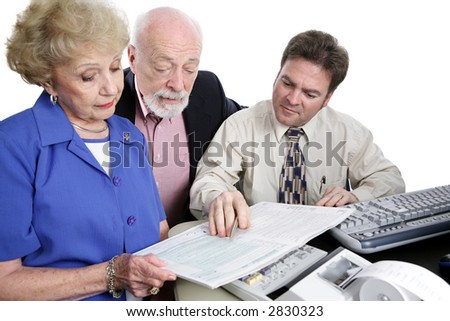 A senior couple going over the tax booklet with their accountant.  Isolated on white.