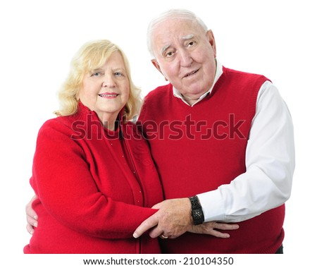 A senior couple happily standing together in their red sweaters.  On a white background. - stock photo