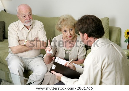A senior couple in marriage counseling.  She's complaining to the therapist about her husband while he looks on in disbelief.  Focus on wife. - stock photo