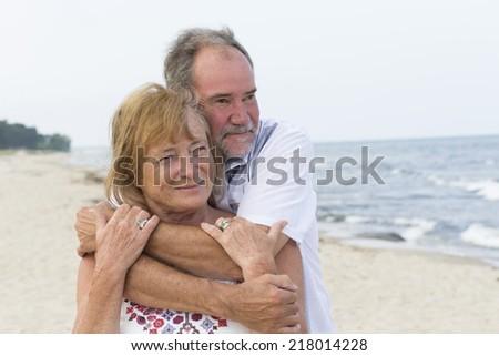 A senior couple on beach hugging - stock photo
