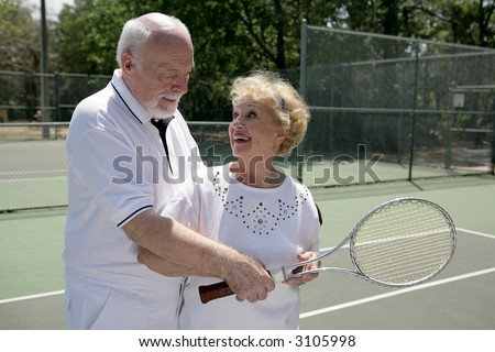 A senior couple playing tennis together.  He's showing her how to grip her racquet. - stock photo