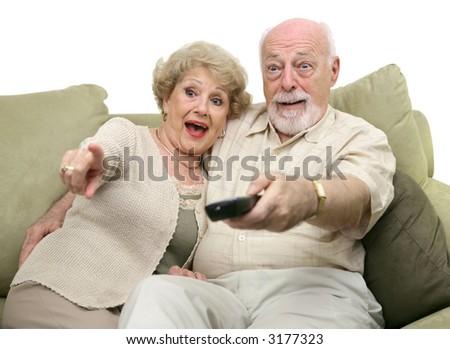 A senior couple really enjoying a television program.  White background. - stock photo