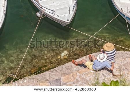 A senior couple relax by the lagoon at Agios Nokolaos on crete. - stock photo