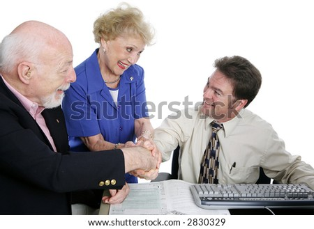 A senior couple shaking hands with their accountant.  Isolated on white. - stock photo