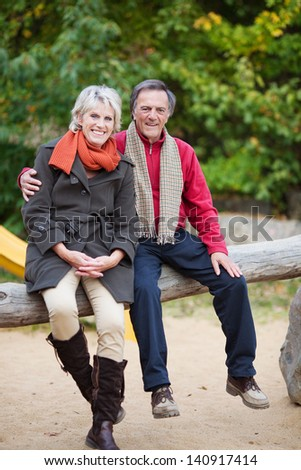 A senior couple Sitting on a tree trunk at a playground