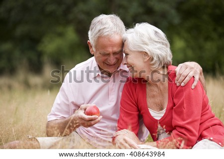 A senior couple sitting on the grass, man holding an apple - stock photo