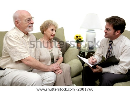 A senior couple speaking with a marriage counselor.  Could also be a salesman in their home.  Isolated on white with focus on couple. - stock photo