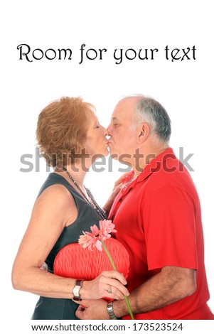 A senior couple still madly in love with each other after almost 40 years of marriage, take a moment to cuddle and kiss for Valentines Day. Isolated on white The Perfect Valentines Day Shot. - stock photo