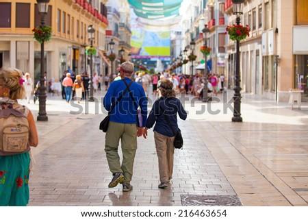A senior couple walking and going sightseeing around Malaga city, Spain. - stock photo