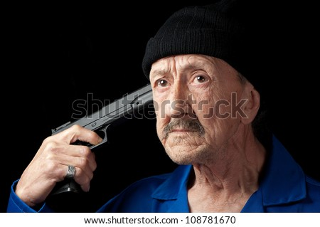 A  senior depressed man contemplates suicide with a pistol. - stock photo