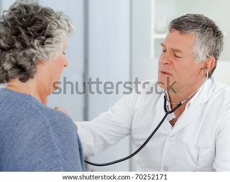 A senior doctor doing an examination of his patient in his office