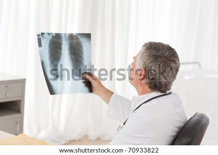 A senior doctor looking at the X-ray in his office - stock photo
