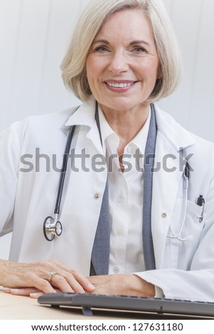 A senior female doctor sitting at a desk in an office with a computer, wearing a suit and stethoscope - stock photo